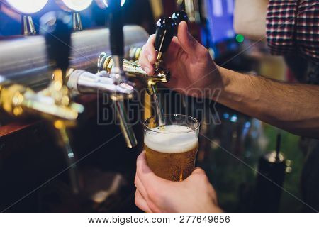 close-up of barman hand at beer tap pouring a draught lager beer. poster
