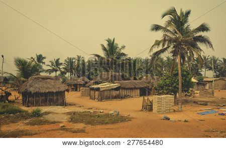 African Village. Houses And Barracks With Thatched Roof With Palm Trees In Background. Rural Lifesty