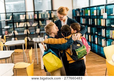 Happy Schoolchildren With Backpacks Hugging Librarian In Library