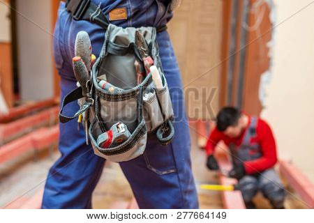 Construction Worker With Workwear And Tool Baf With Tools On The Waist  In Apartment Is Inder Constr