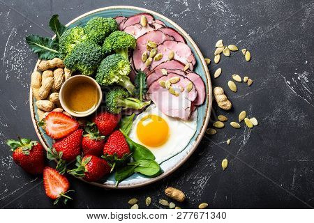 Ketogenic Low Carbs Diet Concept, Top View. Plate On Stone Black Background With Keto Foods: Egg, Me
