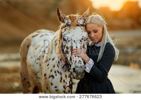 Beautiful Blond Woman In Old Fashioned Dress Embracing Spotty Horse With Eyes Closed In Sunlight