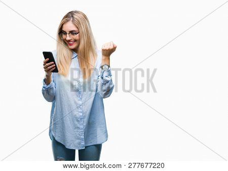 Young beautiful blonde business woman using smartphone over isolated background screaming proud and celebrating victory and success very excited, cheering emotion