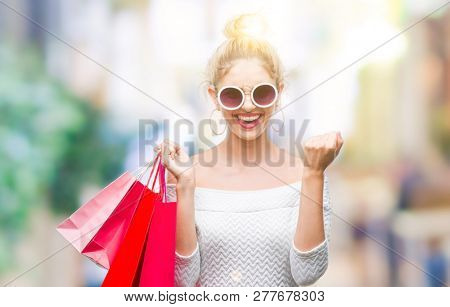 Young beautiful blonde woman holding shopping bags over isolated background screaming proud and celebrating victory and success very excited, cheering emotion