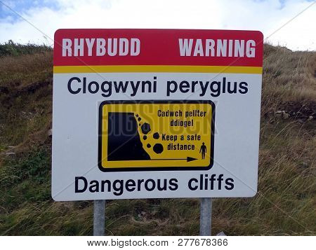 A Warning Sign On A Cliff Edge In South Wales, United Kingdom Depicting Dangerous Cliffs With Text I