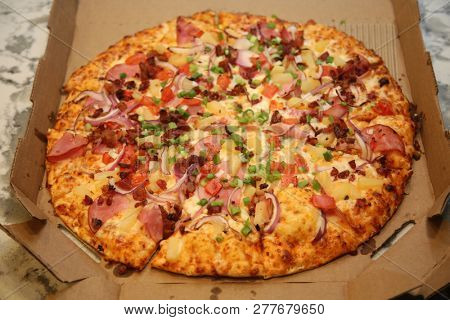 Pizza. Hawaiian Pizza. Pineapple Pizza. Pizza with pineapple, ham, onions, cheese, tomatoes, bacon, and sauce.