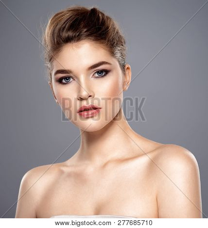 Beautiful face of young caucasian woman with perfect health skin - over grey background. Skin care concept. Attractive Female Model - closeup portrait.