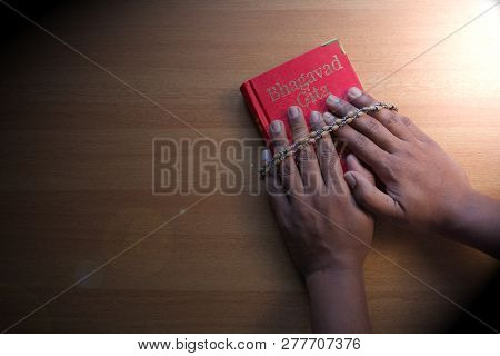 Maski,karnataka,india - December 29,2018 : Holding Bhagavad Gita With Hands On Textured Background