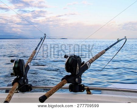 Two Fishing Rods Held In Fishing Rod Holders, Attached To A Back Of A Boat.  The Rods Are Bent From