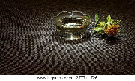 A Dried Yellow Safflower Flower Next To A Glass Cup Filled With Oil On A Dark Cloth Is Highlighted B