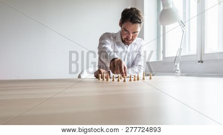 Young Business Executive Positioning White Chess Pieces In A Sensible Structure On His Office Desk I