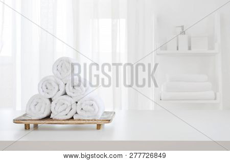 White Towels On Wooden Pedestal Over Blurred Spa Room Background