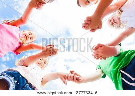 Children Standing In A Circle Holding Hands, Bottom View