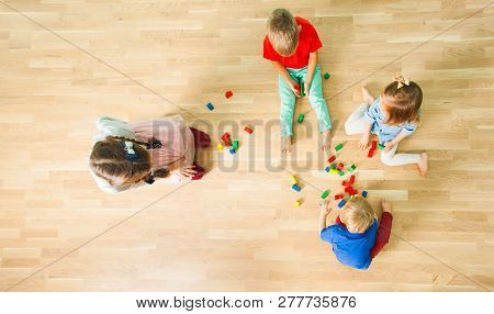 Top View Of Four Kids Constructing Of Wooden Blocks
