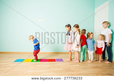 Kids Barefoot Stand In A Row Between Massage Mats
