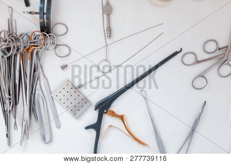 Chrome stainless steel instruments for microsurgery: scalpel, spatula, forceps, forceps, amp, surgical tweezers and scissors, located on the table. poster