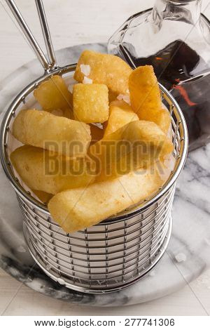 French Fries In A Serving Basket, Served With Malt Vinegar In A Bottle