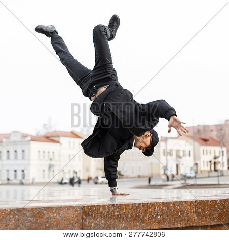 Stylish Young Man Dancer In Black Jeans In A Stylish Jacket In A Cap In Sunglasses Does A Handstand