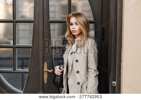 Stylish Attractive Young Blond Woman In An Autumn Coat With A Black Leather Stylish Bag Stands Near