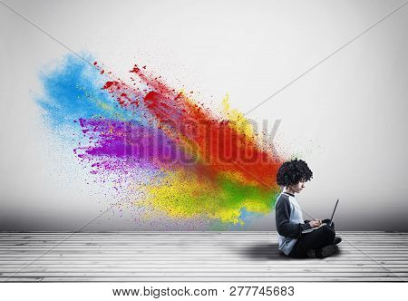 Young Man Working On Laptop And A Powder Explosion .