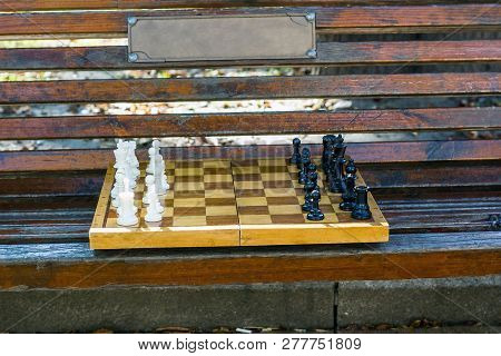 Old Chess On Wooden Bench In Public City Park. Beginning Of Game