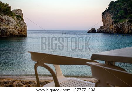 Plastic Chairs And Table Facing The Ocean. Far Shot Of One Small Boat In The Middle And Two Cliffs S