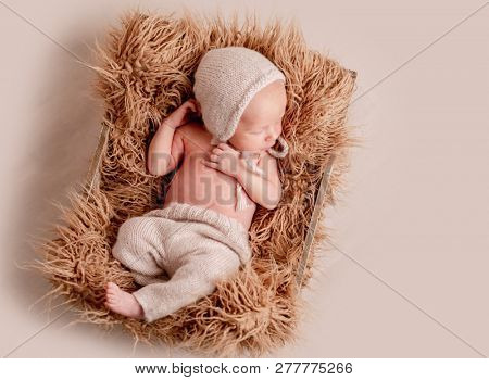 Little cute baby in hat lying covered with light blanket