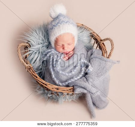 Top view of baby in big hat sleeping in basket covered in blue blanket