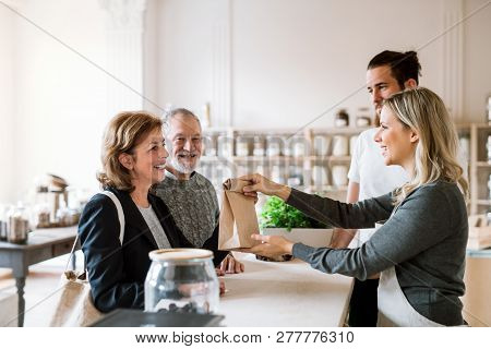 Senior Couple Buying Groceries In Zero Waste Shop, Sales Assistants Serving Them.