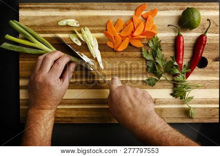 Plan View Of Hands Chopping A Variety Of Vegetables, On A Chopping Board