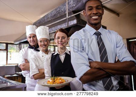 Group of hotel staffs standing with armas crossed in kitchen at hotel