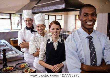 Group of hotel staffs standing with arms crossed in kitchen at hotel
