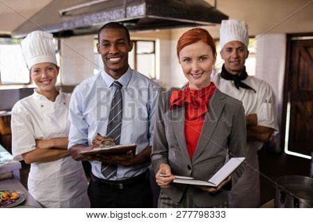 Group of hotel staffs standing in kitchen at hotel