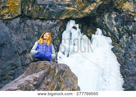 Freedom Traveler Woman Standing. Female Hiking Around Mountains And Stands Behind A Frozen Waterfall