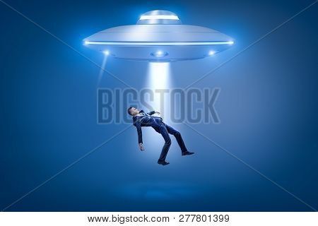 A businessman pulled toward an open hatch of a UFO by some invisible force. poster