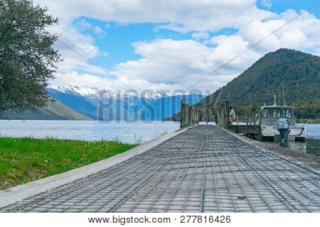 Lake Rotoroa New Zealand - October 6 2018; Two Tourists On Pier Extending Into Scenic Lake With Boat