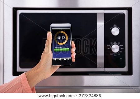 Close-up Of A Person Hands Operating Oven Application With Mobile Phone