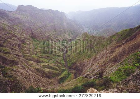 Breathtaking Panorama Of A Steep Gorge With Haze Riverbed And Lush Green Vegetation In The Valley Of