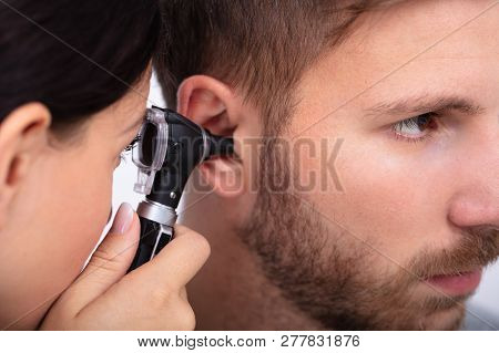 Doctor Examining Male Patient's Ear