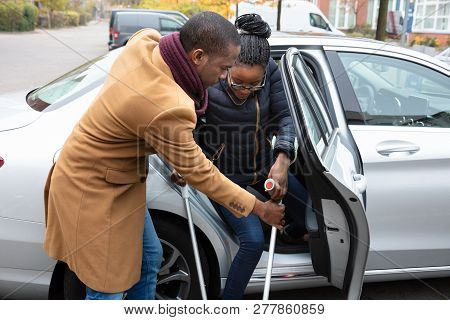 Young African Man Helping Her Disabled Wife With Crutches To Get Out Of A Car