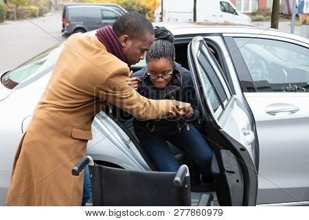 African Man Assisting Her Handicapped Wife To Get Out Of A Car