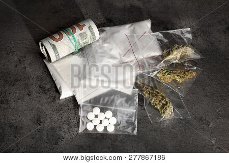 Plastic Bags With Cocaine, Pills, Hemp Buds And Money On Grey Background