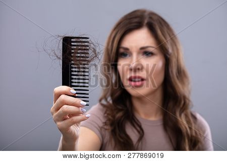 Close-up Of A Worried Woman Holding Comb Suffering From Hairloss