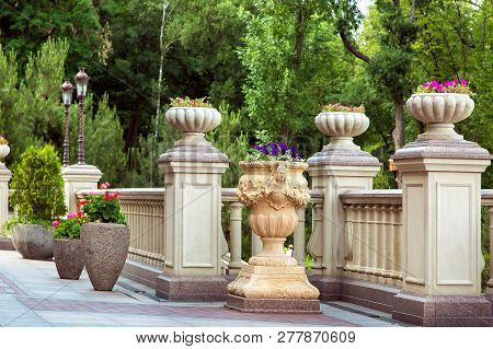 Stone Flowerpots With Flowers On Pedestals Between Railings With Baroque Balustrades, Retro Lantern