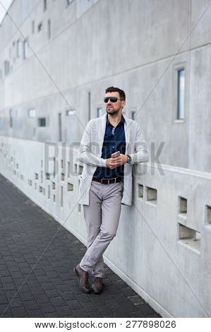 Full Length Portrait Of Handsome Business Man With Smart Phone Standing Over Modern Building