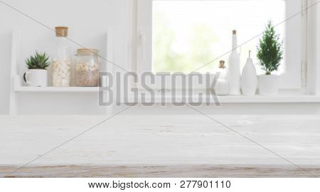 Wooden Tabletop In Front Of Blurred Kitchen Window And Shelves