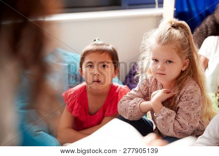 Two infant school girls sitting on bean bags in a comfortable corner of the classroom listening to their teacher reading a story, view over teacherÕs shoulder