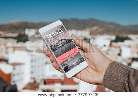 Man Holding A Mobile Phone In The Hand With Travel News Website In The Screen, With City Background.