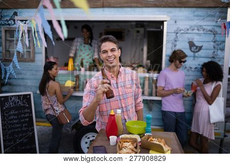 Portrait of happy man holding beer bottle in cafeteria