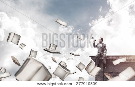 Young Businessman Sitting On Building Top And Screaming Emotionally In Megaphone